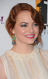 Emma Stone pumped up her neutral dress with green earrings.