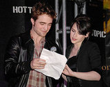 Robert Pattinson and Kristen Stewart helped each other while speaking at a Hot Topic store during the New Moon press tour in 2009.