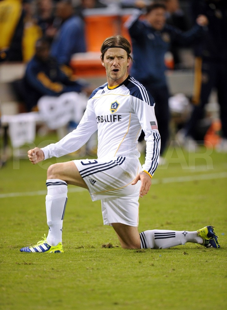 David Beckham stretched on the soccer field.