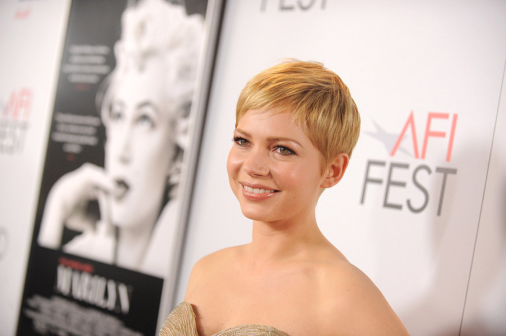 Michelle Williams posing in front of her poster for My Week With Marilyn.
