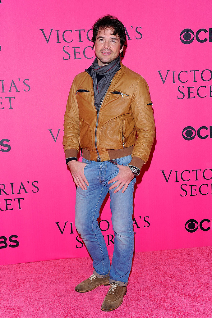 Matthew Settle in a brown leather jacket.