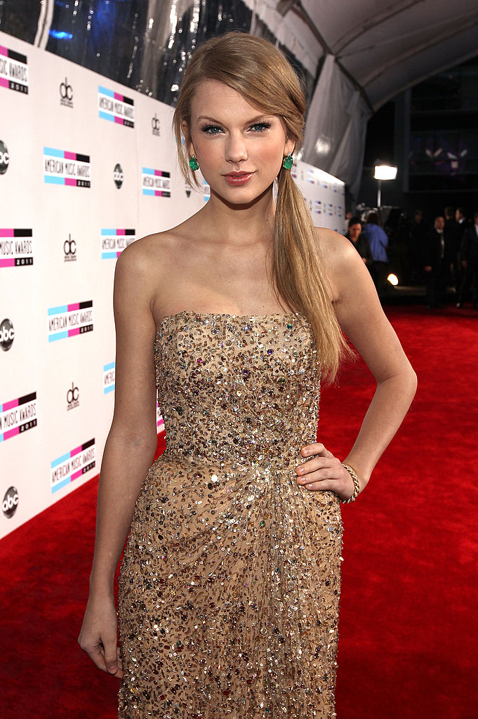 Taylor Swift walked the red carpet wearing gold at the AMAs.