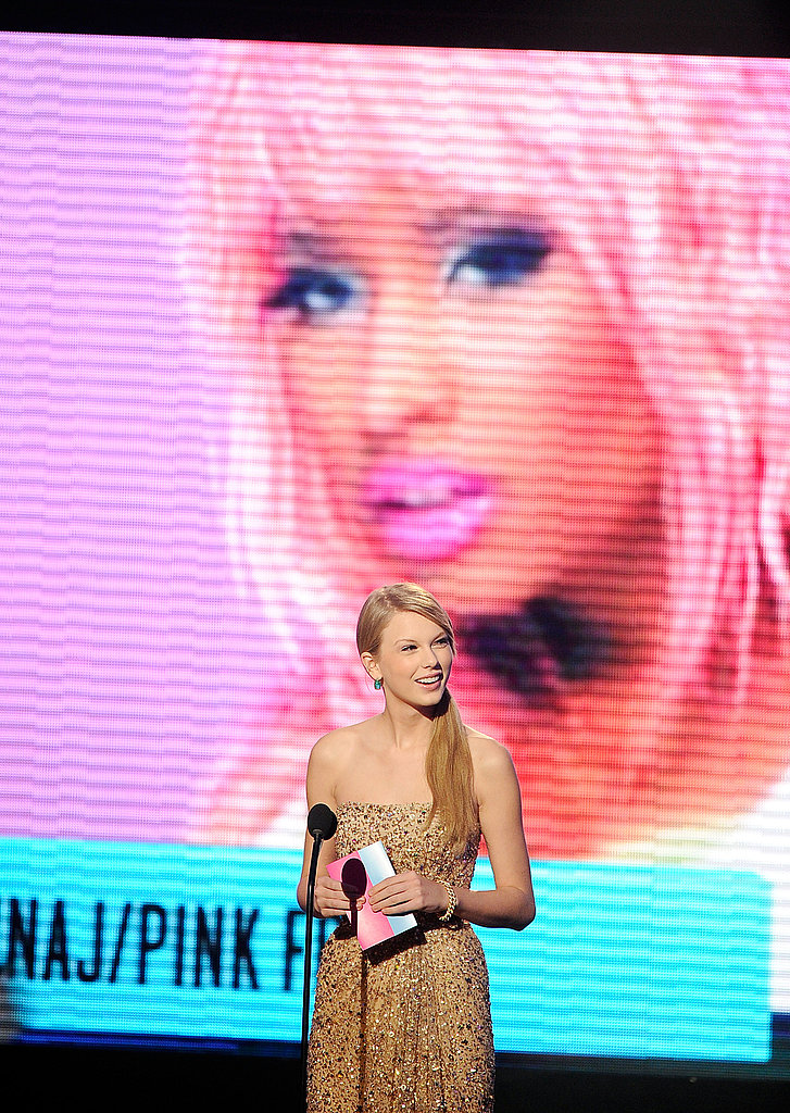 Taylor Swift stood in front of a screen of Nicki Minaj.
