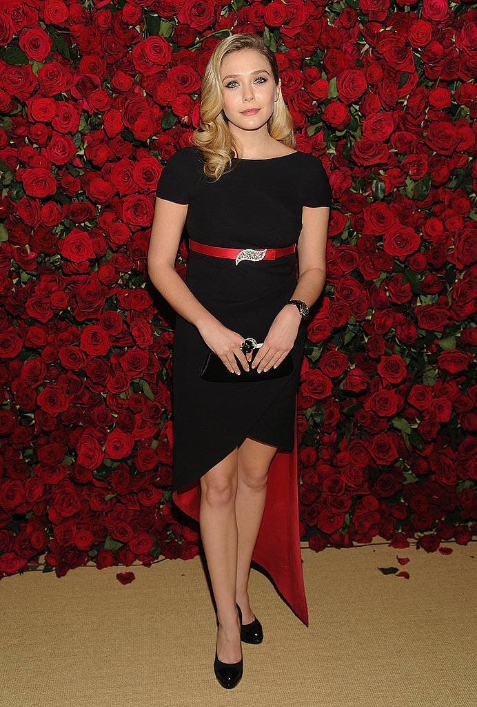Elizabeth Olsen posed in front of a rose wall at NYC's MoMA.