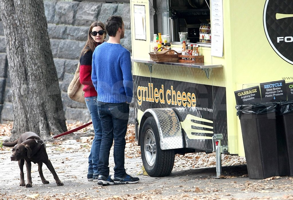 Newly engaged Adam Shulman and Anne Hathaway stopped by an NYC food truck with their chocolate Lab, Esmeralda.