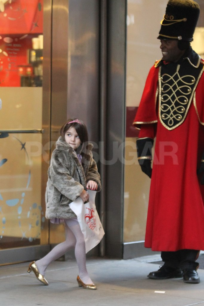 Suri Cruise carried her own shopping bag out of a store.