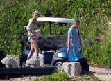 George Clooney and Stacy Keibler walked to a golf cart.