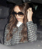 Victoria Beckham brushed her curled hair out of her face.