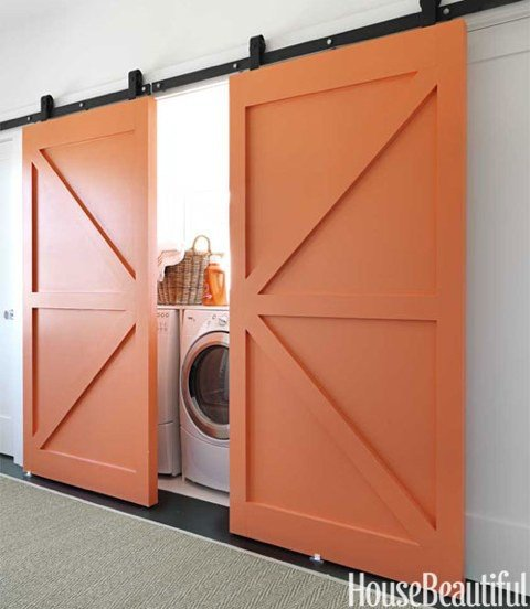 Coral paint gives these barn doors a modern twist — a stylish way to conceal a laundry nook while introducing color to a room.  Source