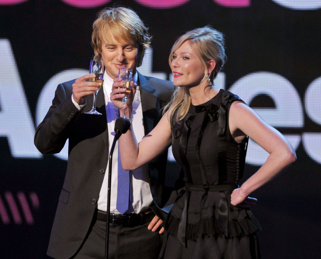 Owen Wilson giggles while toasting with Kirsten Dunst.