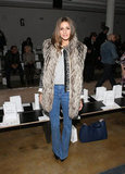 Olivia showed off her chic '70s style in flared denim jeans and an oversize furry vest.
