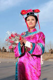 A woman wearing a Qing dynasty dress hands out roses to couples for free in Beijing.