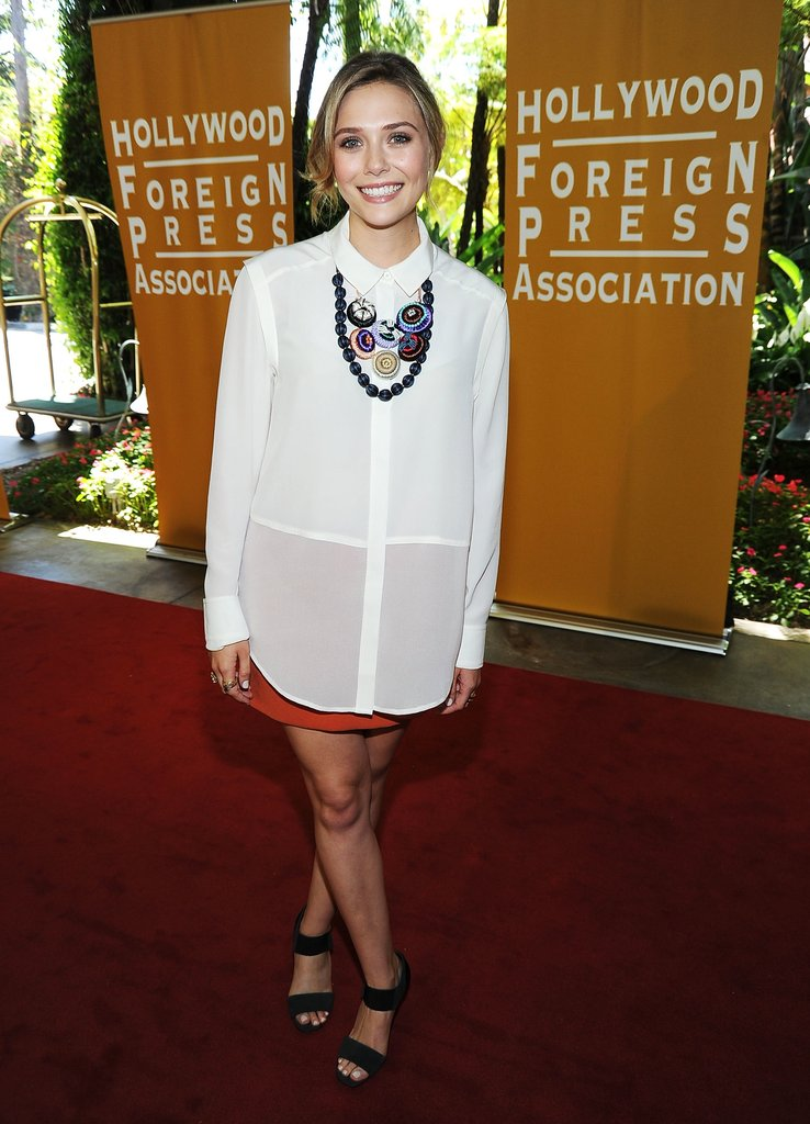 At the Hollywood Foreign Press Association event, one of her first red-carpet appearances, Elizabeth opted for an easy glam ensemble: sheer white button-down tunic, orange miniskirt, and a bib and bead necklace.         Longsleeve Tops by Rag and BonePlatforms by Pilar Abril