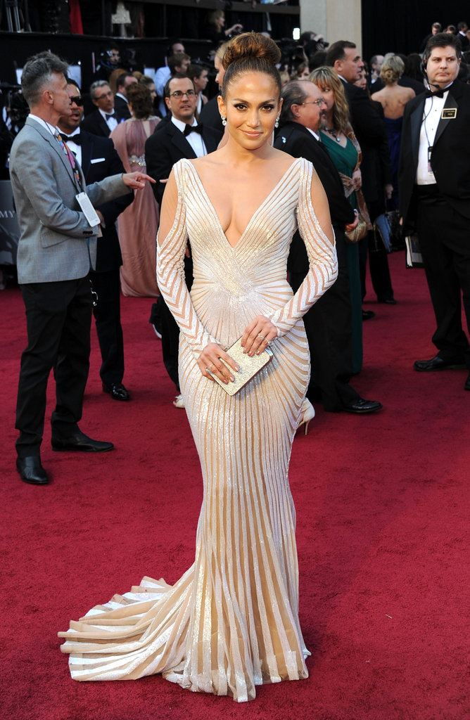Jennifer Lopez turned up the sexy on the Academy Awards red carpet, opting for high-wattage glamour in a silvery Zuhair Murad gown. It was a serious dose of sultry via a low neckline — and backline — and revealing arm cutouts, not to mention sheer insets throughout the whole design.