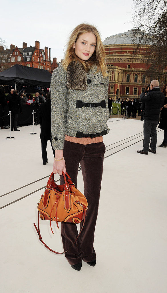 Rosie Huntington-Whiteley bundled up in velvet pants and a cozy knit jacket outside the Burberry show.