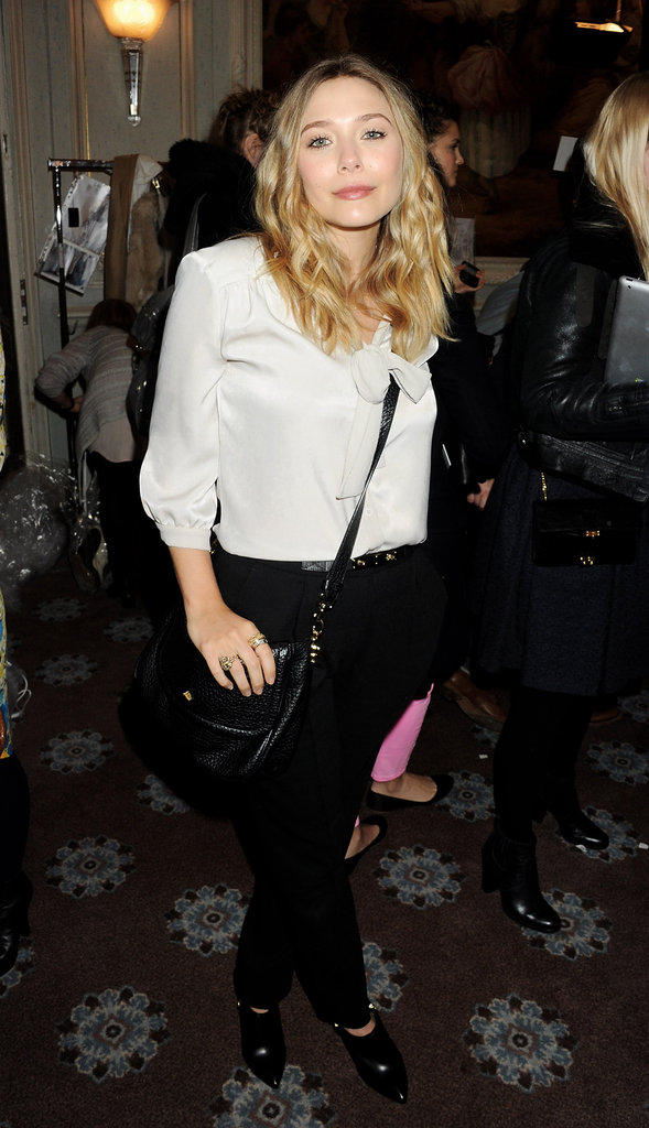 Elizabeth Olsen outfitted an easy look in a white silky blouse and black trousers at Mulberry.