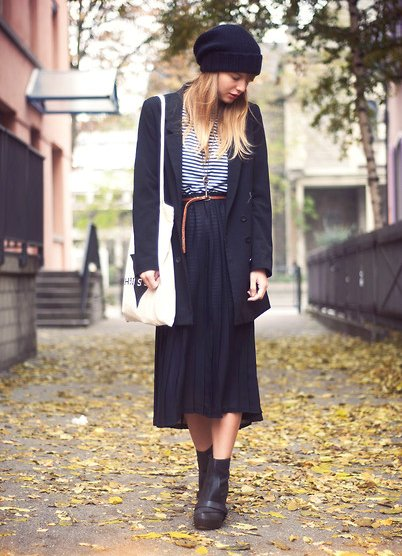 Adding cozy edge (literally), this street styler shifts the focus of a pleated skirt from femme to street cool with a knit beanie, buckled boots, and borrowed-from-the-boys outerwear.  4775072  Photo courtesy of Lookbook.nu