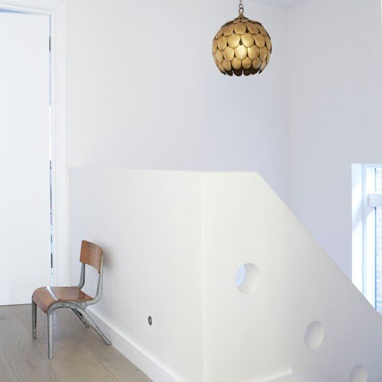 Sometimes, a moment of minimalism in a hallway can leave an even bigger impact than a richly decorated one. I love how a golden artichoke pendant, single vintage chair, and peek-a-boo holes along the staircase hold equal interest.  Source