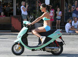 Selena Gomez wearing a bikini and riding a scooter.