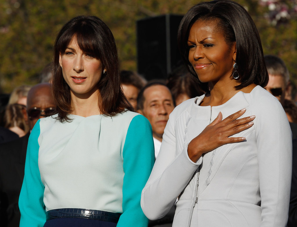 Michelle Obama puts her hand over her heart.