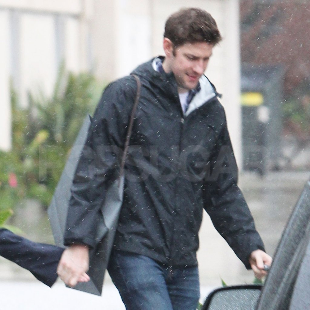 John Krasinski carried a dark shopping bag.