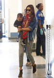 Miranda Kerr perfected travel style in a pair of easy knit trousers dressed up with a pair of suede ankle boots.
