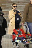 Natalie Portman wore a tan coat and Converse sneakers for her travels while carrying Aleph through the airport.