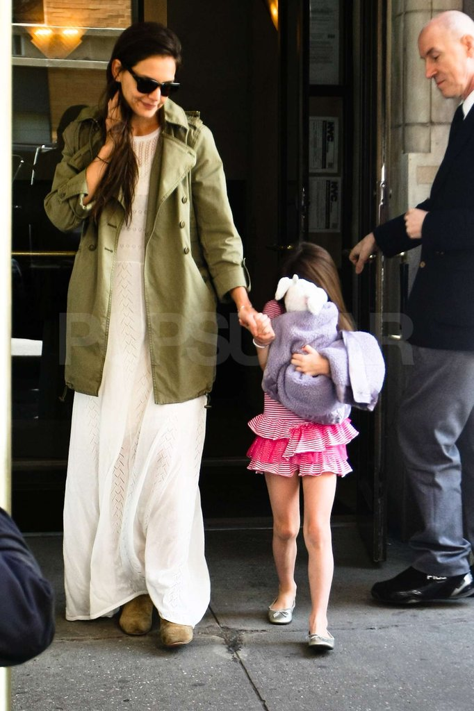 Katie Holmes wore a green trench coat and Suri Cruise held tight to a stuffed animal on her 6th birthday in NYC.