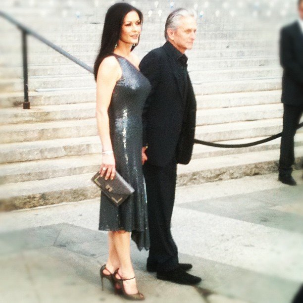 Catherine Zeta-Jones and Michael Douglas hurried into the Vanity Fair party — but first! — we got a quick shot of her sequined, one-shoulder Michael Kors dress and gold Christian Louboutin heels.
