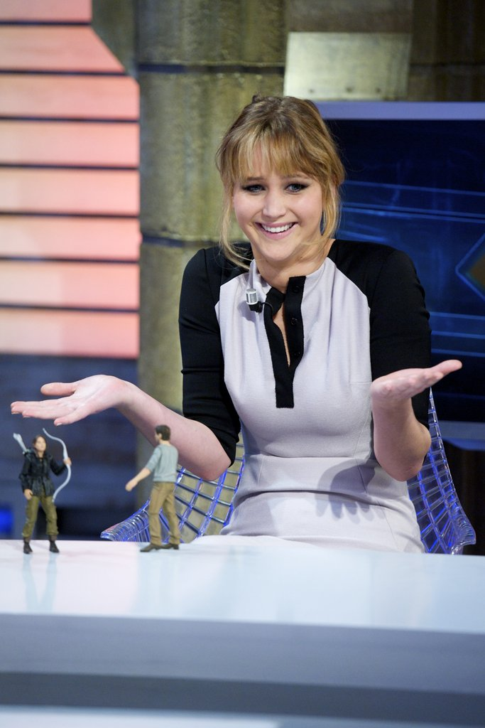 Jennifer Lawrence shrugged in confusion while two Hunger Games action figures sat in front of her.