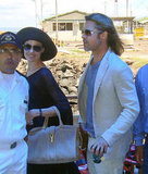 Angelina Jolie wore a black large-brimmed hat and carried her YSL bag accompanied by Brad Pitt while traveling back from the Galapagos Islands in April 2012.