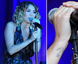Miley Cyrus has an anchor on her wrist and a small heart on her pinky finger.
