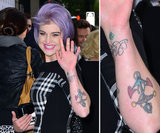 Kelly Osbourne has multiple tattoos on her left arm including an anchor and script.