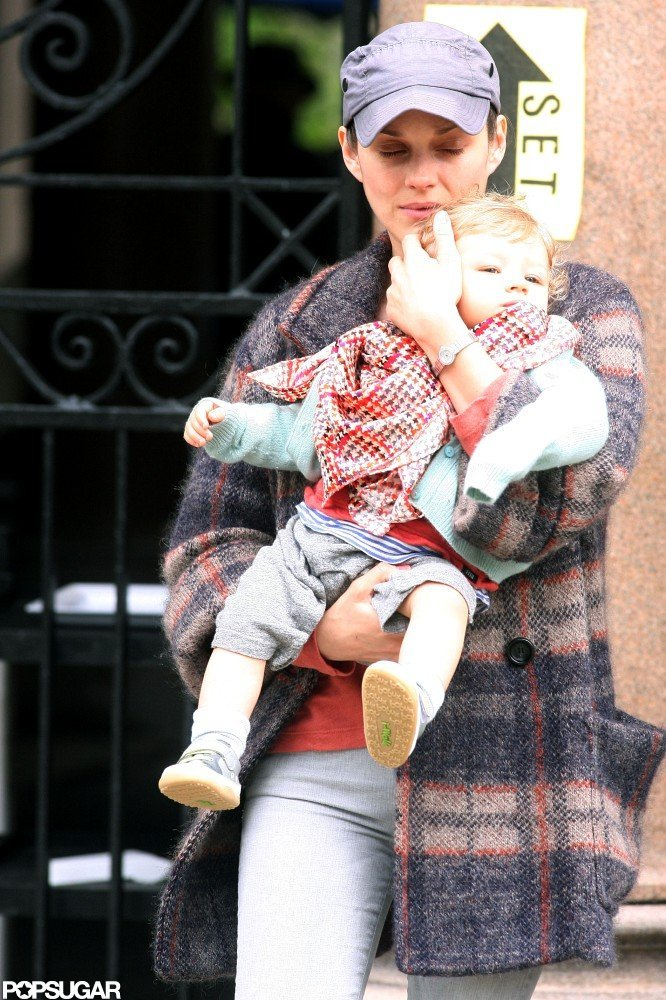 Marion Cotillard wore a blue baseball cap while she held her son Marcel on set in NYC.