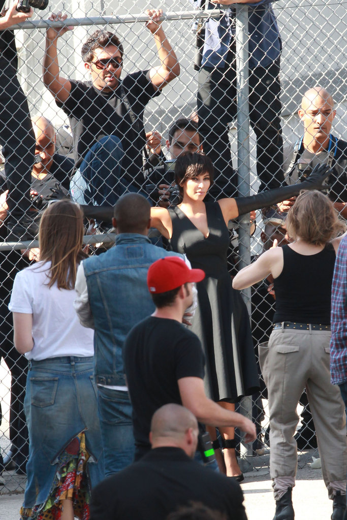 Kim Kardashian stretched out her arms against a fence for a photo.