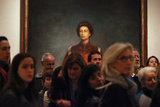A portrait of the queen is seen behind a crowd of visitors to the National Portrait Gallery.