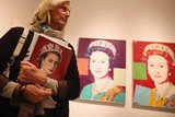 A woman held an exhibition catalog in front of an artwork by Andy Warhol.