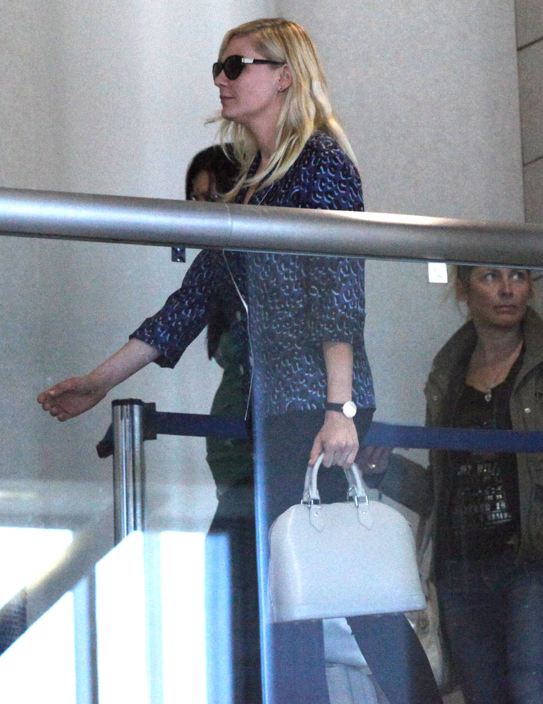 Kirsten Dunst walked toward her gate.