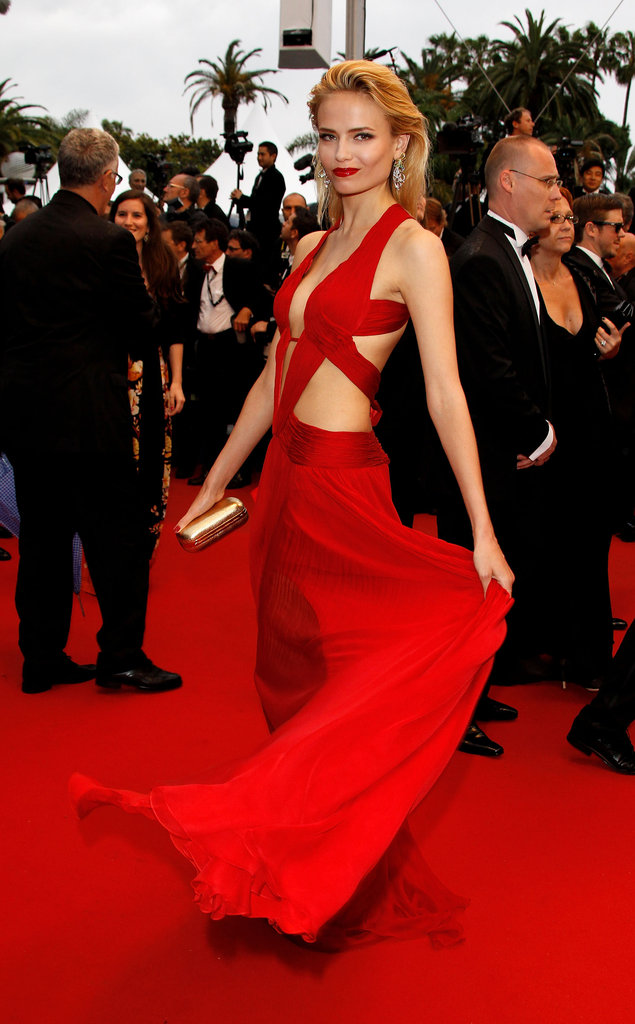 Natasha Poly channeled the sexiest kind of glam in a skin-baring red cutout gown at the Cosmopolis premiere in Cannes.