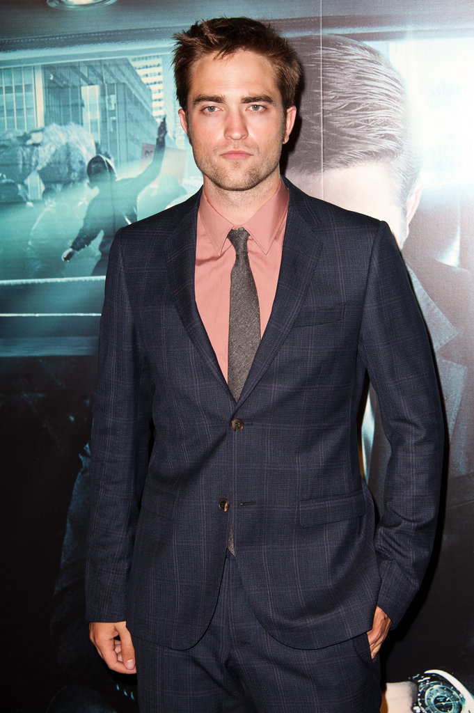 Robert Pattinson wore a navy blue suit and pink shirt on the red carpet at the Cosmopolis premiere.