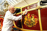 The carriage restorer carefully cleaned a royal carriage.