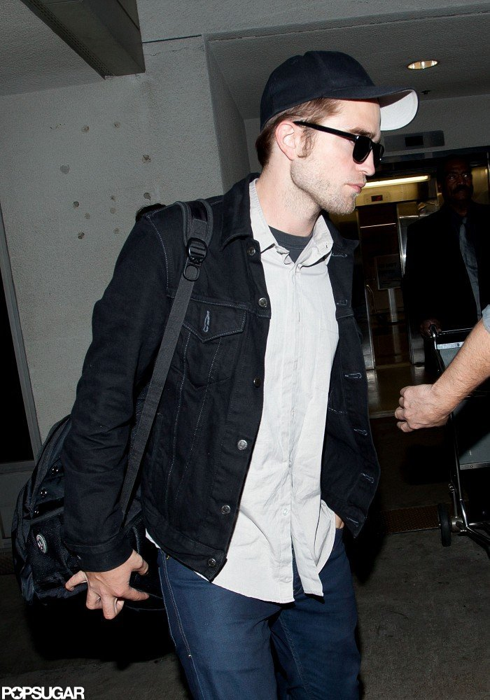 Robert Pattinson wore a black hat and sunglasses through the airport in LA.