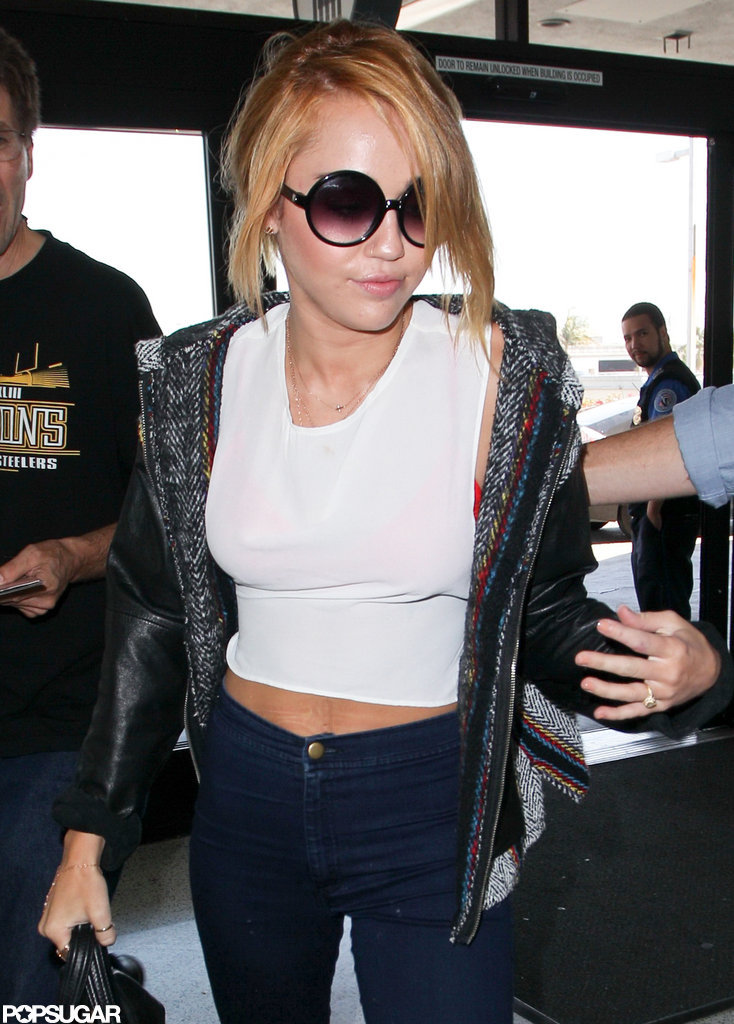 Miley Cyrus showed off her engagement ring boarding a plane at LAX.