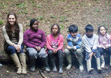 Kate Middleton sat on a log with children from Expanding Horizons' primary school outdoor camp.