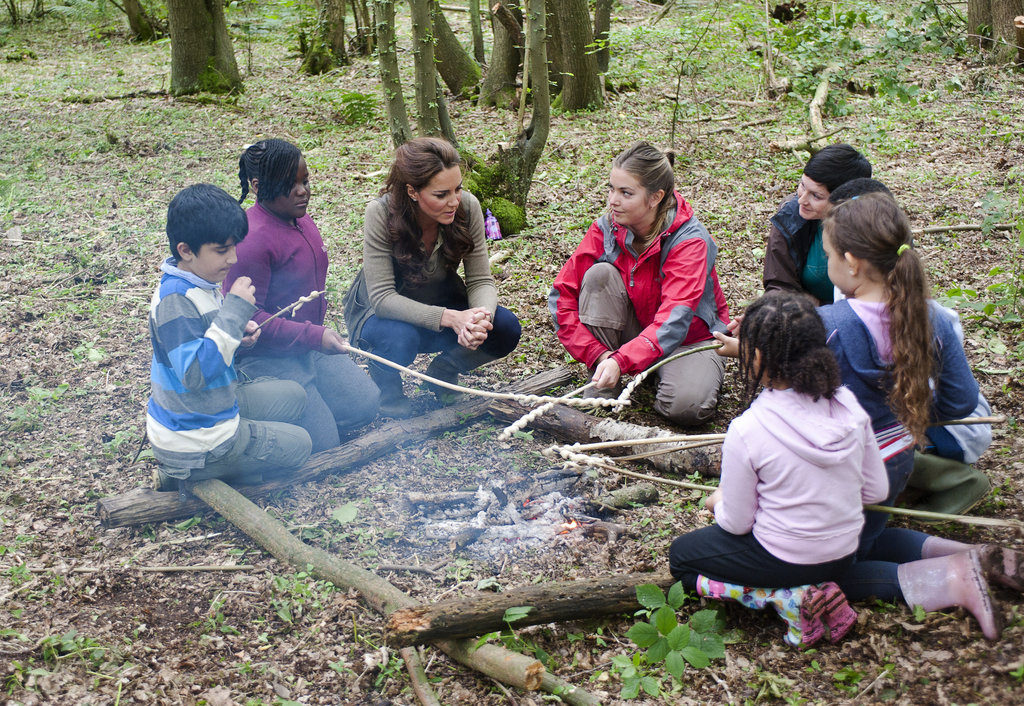 Kate Middleton sat by a fire with children from Expanding Horizons primary school outdoor camp.