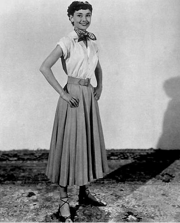 Audrey Hepburn's sweet-feeling feminine dressing from Roman Holiday would be right on trend today. Her must-mimic formula centered on a classic blouse, a full skirt, and lace-up Summer sandals.