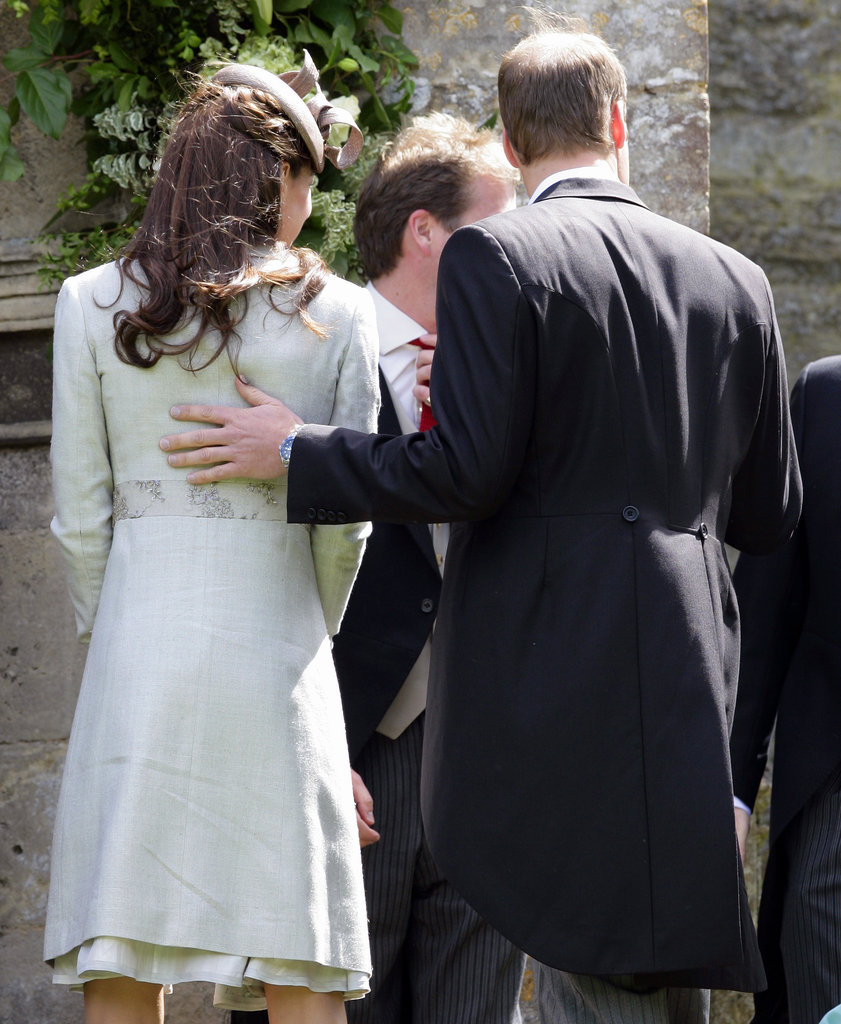 William rested his hand on Kate's back at a wedding in June 2012.