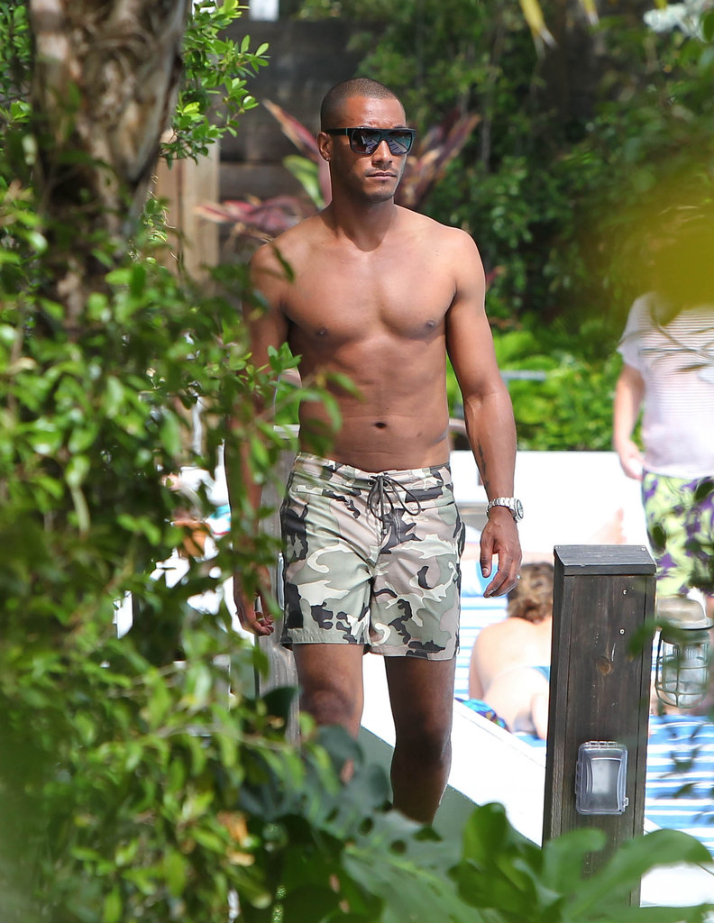 Shirtless Sunnery James walked around the pool.