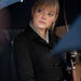 Emma's character, Gwen, wearing a chic houndstooth blouse, black coat, and black leather gloves. 