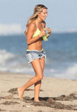 Ashley Tisdale wore a green bikini with fringe and denim shorts on the beach in Malibu.